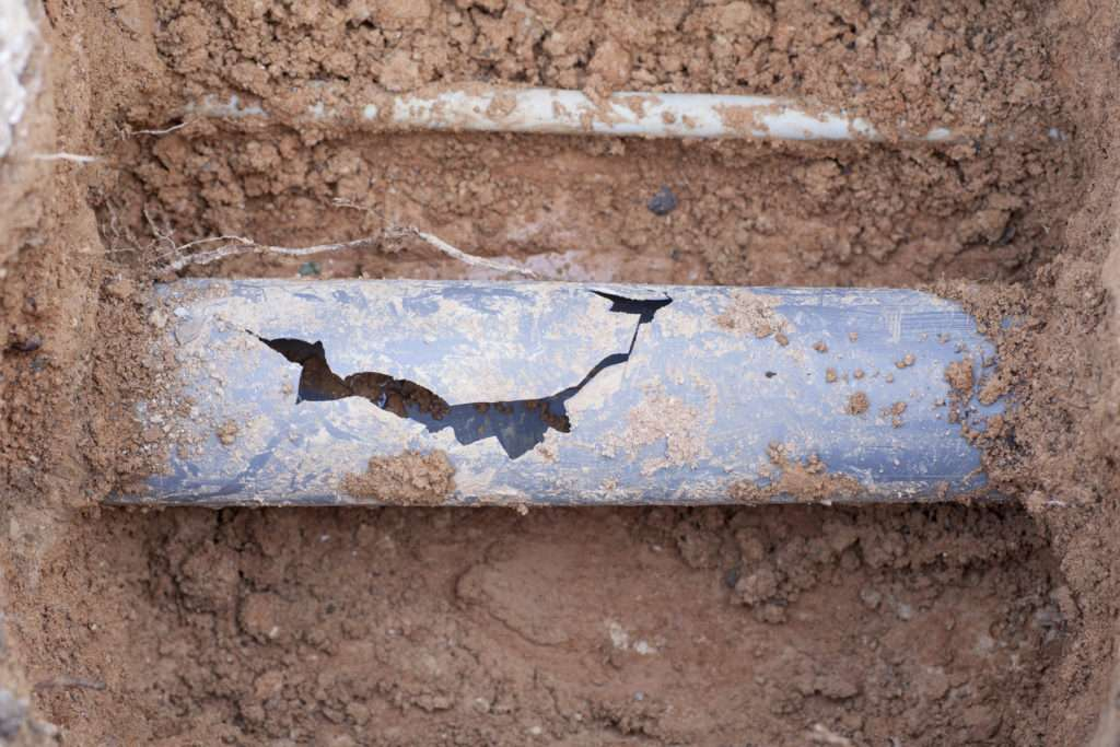 Cracked sewage pipe in ground